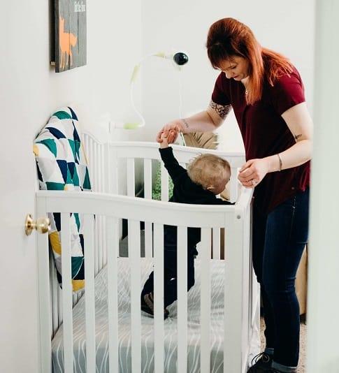 תינוק עומד בעריסה